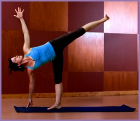 Young woman doing Half Moon Pose in a yoga studio
