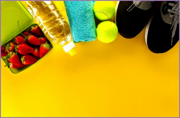 healthy life sport concept sneakers with fruits towel and bottle of water on wooden background copy space