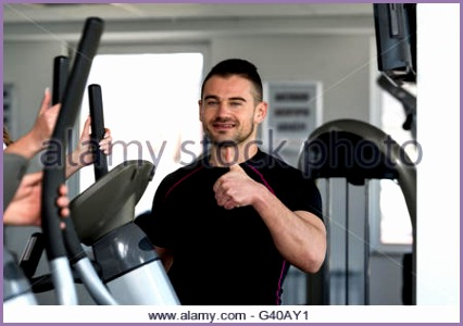 stock photo mature woman exercising triceps on cable machine in the gym and flexing
