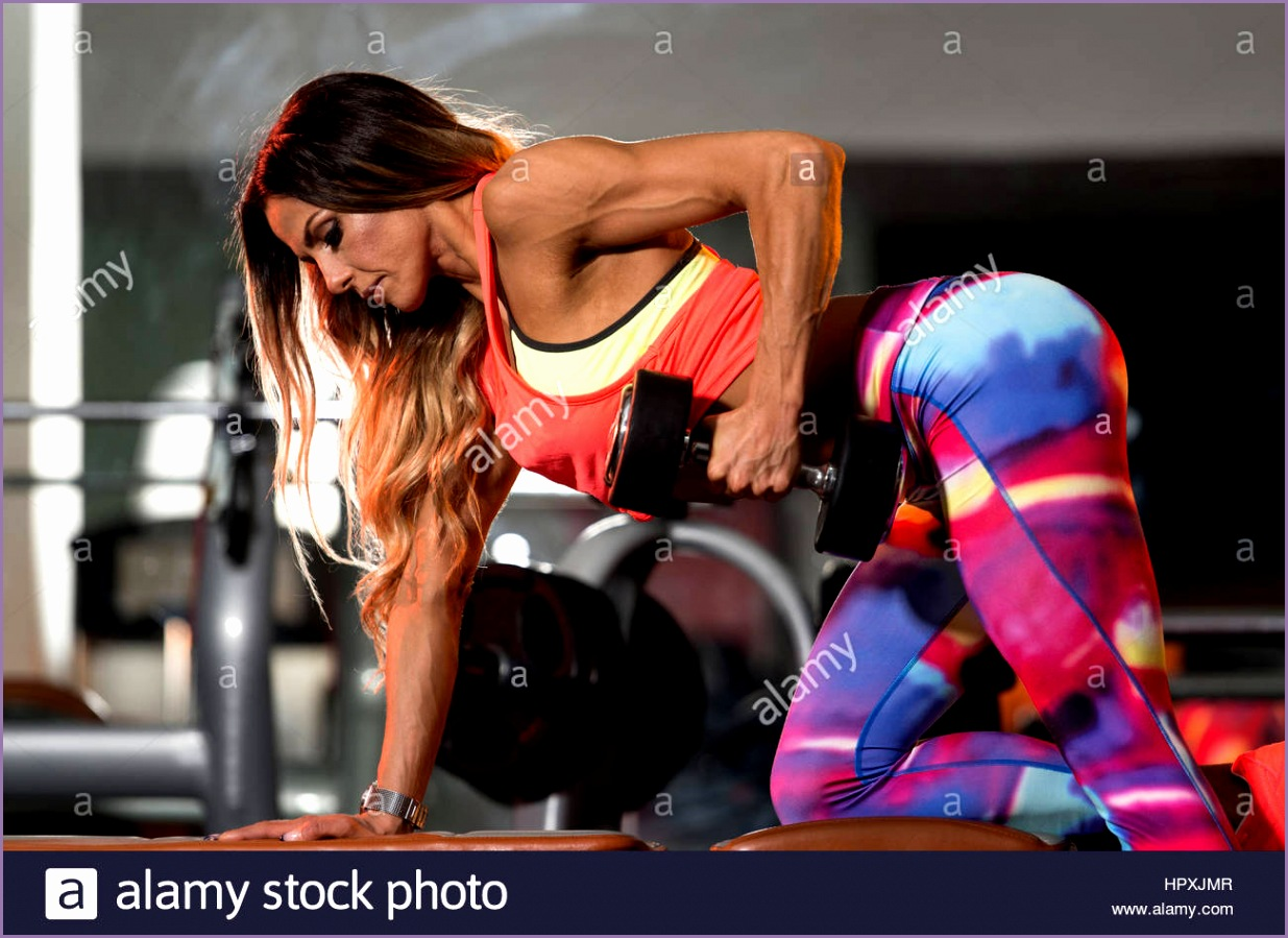stock photo woman exercising back with dumbbells in the gym and flexing muscles